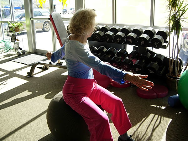 Older woman sitting on fitness ball